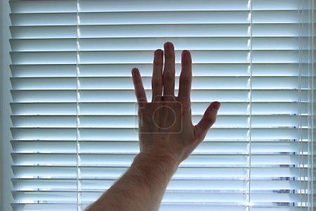 Hand on white blinds background