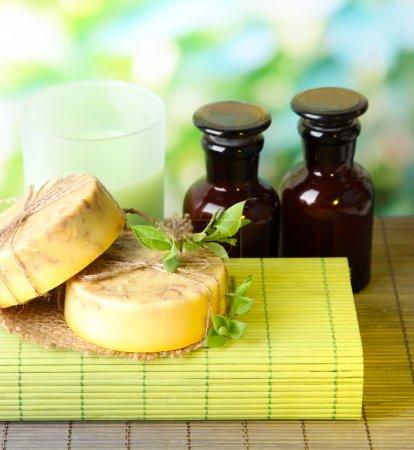 Photo pour Ingrédients pour le savon sur la natte de bambou, sur fond vert et du savon fabriqué à la main - image libre de droit