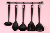 černá kuchyně nádobí na stříbrné háčky, na růžovém pozadí