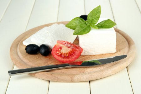 Sheep milk cheese, black olives, red tomato with basil on cutting board, isolated on white