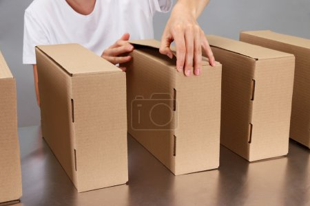Worker working with boxes at conveyor belt, on grey background