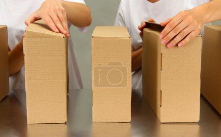 Photo pour Travaillant avec des boîtes à bande transporteuse, sur fond gris - image libre de droit