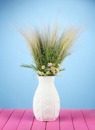 Photo pour Bouquet de fleurs sauvages et d'herbes, en vase, sur table en bois sur fond de couleur - image libre de droit