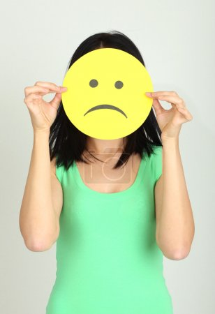 Photo for Young woman holding paper with sad smiley on gray background - Royalty Free Image