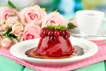 Tasty jelly dessert with fresh berries, on bright background