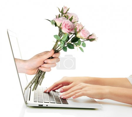 Male hand giving flowers to woman from laptop screen isolated on white