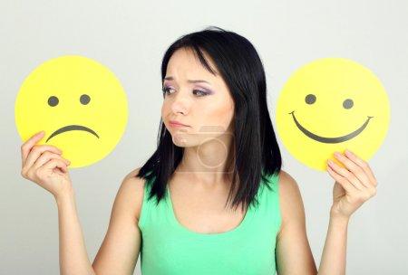 junge Frau hält Papier mit traurigem und glücklichem Smiley auf grauem Hintergrund