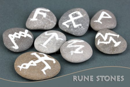 Fortune telling with symbols on stones on grey background