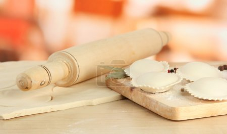 Raw dumplings and dough, on wooden table