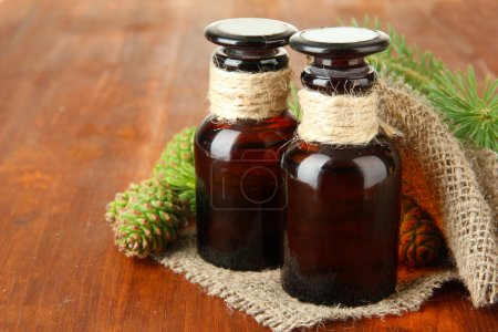 Bottles of fir tree oil and green cones on wooden background