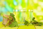 Brýle Březové mízy na dřevěný stůl, na zeleném pozadí