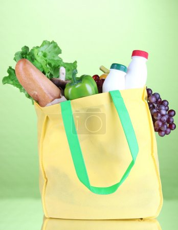 Photo for Eco bag with shopping on green background - Royalty Free Image