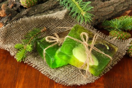 Hand-made soap and green pine cones on wooden table