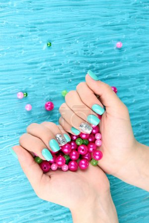 Photo pour Mains de belle femme avec manucure bleu tenant perles roses, sur fond de couleur - image libre de droit