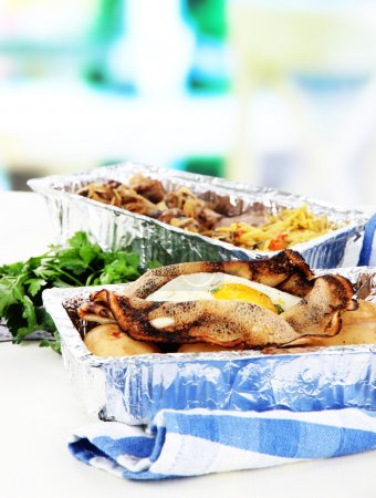 Food in boxes of foil on napkin on wooden board on room background