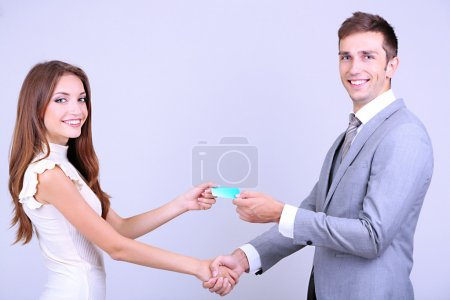 Business partners changing business cards on grey background