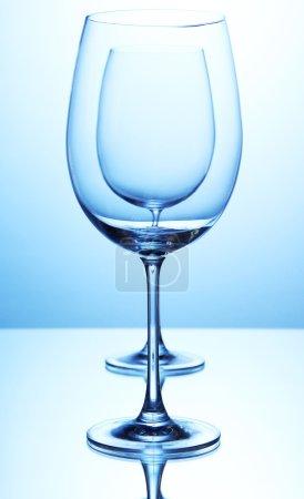 Empty wine glasses arranged on blue background