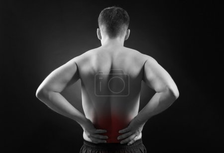 Lower back pain in man on dark background