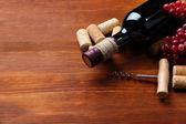 Láhev vína, vinných hroznů a zátky na dřevěné pozadí
