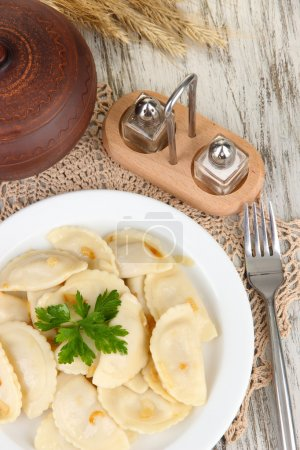 Tasty dumplings with fried onion on white plate, on wooden background