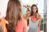 Krásná dívka snaží šaty zrcadla na pozadí místnosti