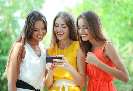 Three beautiful young woman with smartphone in summer park