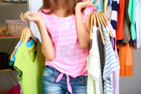 Photo for Beautiful girl with lots clothes in room background - Royalty Free Image