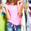 Beautiful girl with lots clothes in room backgroun...