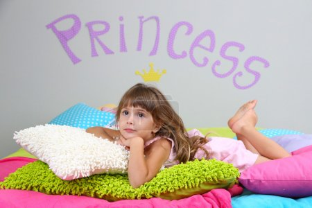 Little girl lying on bed in room on grey wall background