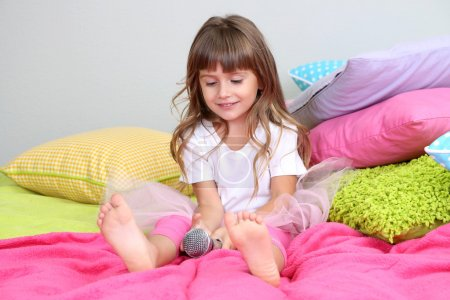 Photo for Little girl sings on bed in room on grey wall background - Royalty Free Image