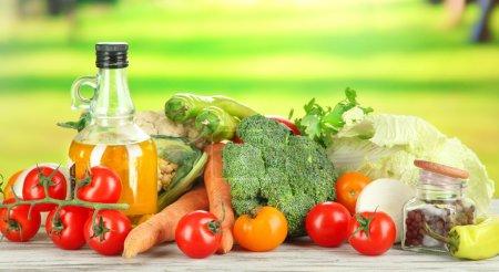 Fresh vegetables in basket on wooden table on natural background