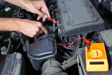 Photo pour Mécanicien automobile utilise voltmètre multimètre pour vérifier le niveau de tension dans la batterie de voiture - image libre de droit
