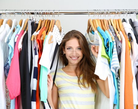 Photo for Beautiful young woman near rack with hangers - Royalty Free Image