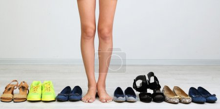 Photo for Girl chooses shoes in room on grey background - Royalty Free Image