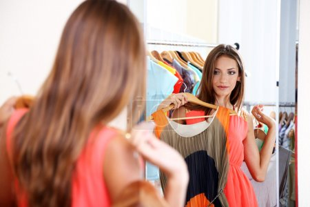 Photo for Beautiful girl trying dress near mirror on room background - Royalty Free Image
