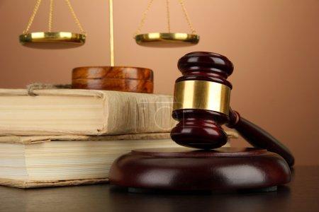 Photo pour Balance d'or de la justice, marteau et livres sur fond marron - image libre de droit