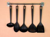 černá kuchyně nádobí na stříbrné háčky na broskvovým pozadím