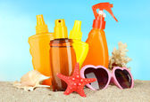 Bottles with suntan cream and sunglasses, on blue background