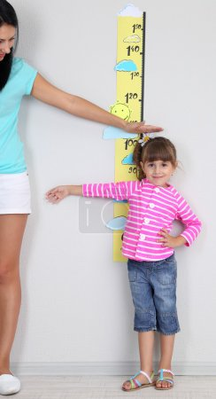 Mom measures growth of daughter in room