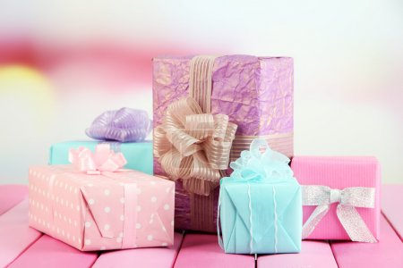 Photo pour Beaux cadeaux lumineux, sur une table en bois claire - image libre de droit