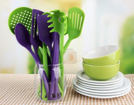 Photo pour Ustensiles de cuisine en plastique dans le stand avec vaisselle propre sur la nappe sur fond lumineux - image libre de droit