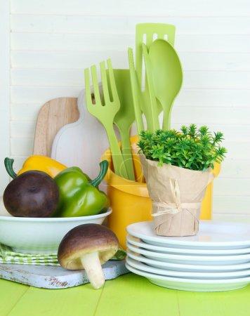 Photo pour Ustensiles de cuisine en plastique dans une tasse sur une table en bois - image libre de droit