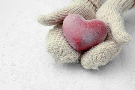 Photo pour Femelle les mains dans les mitaines avec coeur rouge, gros plan - image libre de droit