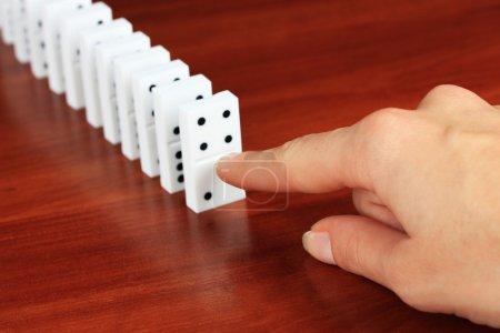 Photo pour Main poussant dominos sur fond en bois - image libre de droit