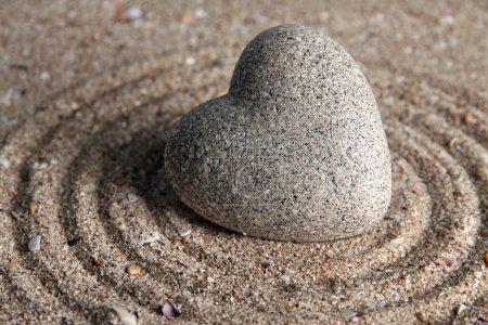 Photo pour Pierre zen grise en forme de coeur, sur fond de sable - image libre de droit
