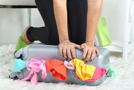 Photo pour Valise avec vêtements sur tapis sur fond de chambre - image libre de droit