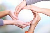 Lidské ruce takže kruh na světlé pozadí
