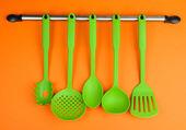 Plastové nádobí na stříbrné háčky na oranžovém pozadí