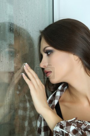 Photo for Lonely sad woman looking through window - Royalty Free Image
