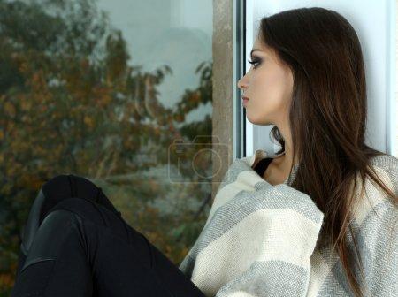 Mujer triste solitaria mirando por la ventana